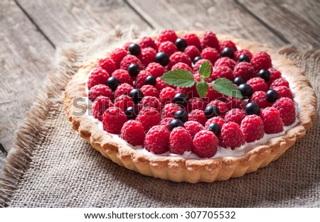 Delicious traditional homemade sweet raspberry tart cake dessert. Creamy pie with raspberries, whipped cream and mint on vintage rustic background. Rustic style and natural light. - stock photo
