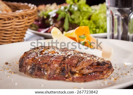 Delicious trimmed lean portion of thick grilled beef steak with seasoning served on a white plate, close up with shallow dof