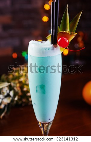 Delicious tropical blue curacao alcoholic cocktail garnished with a fresh pineapple slice and maraschino cherries on a table in the restaurant with bright backgrounds of disco lights. soft focus - stock photo