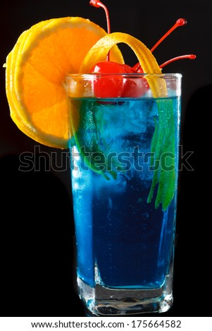 Delicious tropical iced blue curacao cocktail garnished with a fresh orange slice and maraschino cherries on a black background - stock photo