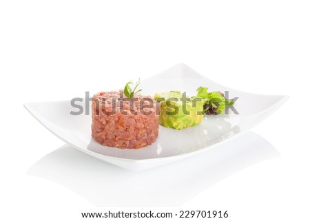 Delicious tuna steak tartare with avocado dip and fresh green salad on plate on white background. Fine dining. - stock photo
