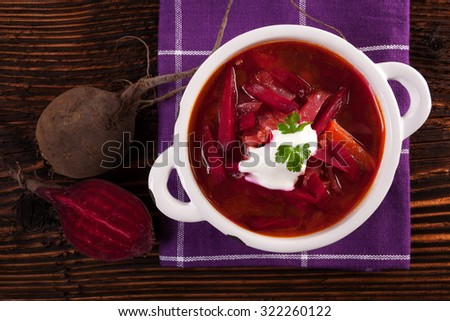 Delicious ukrainian borsch soup with fresh beetroot vegetable on purple cloth on rustic wooden table, top view. Traditional european cuisine. - stock photo