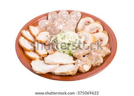 Delicious ukrainian cold cuts platter. Served with marinated onions on brown clay plate. Isolated on a white background.