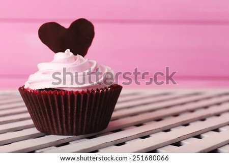 Delicious Valentine Day cupcake on pink wooden background - stock photo