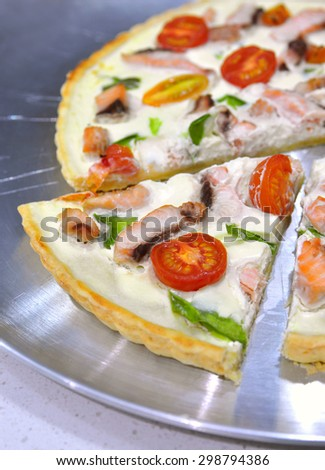 Delicious variation for quiche pie and pizza - pie with thickened cream and cottage cheese, salmon, green capsicum and cherry tomatoes cut in halves. Selective focus, copy space - stock photo