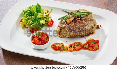 delicious veal steak with salsa sauce and salad on a white plate.