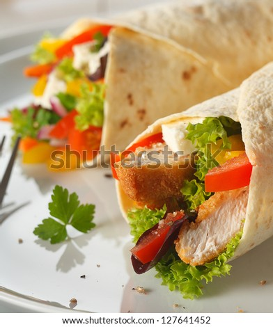 Delicious vegetarian pancake wraps filled with feta cheese, salad and crusty bread chunks, closeup view on a plate