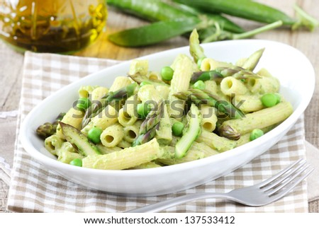 Delicious vegetarian pasta with fresh asparagus and green peas sauce - stock photo