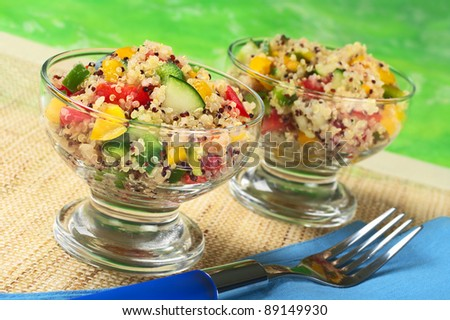 Delicious vegetarian quinoa salad in glass bowls with bell pepper, cucumber and tomatoes (Selective Focus, Focus on the salad in the front of the left bowl) - stock photo