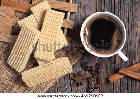 Delicious wafers and cup of hot coffee for breakfast on rustic wooden table