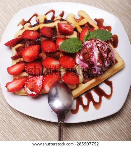 delicious waffles on white plate with strawberry and ice cream - stock photo