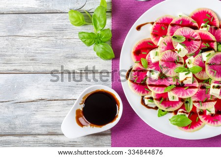 delicious watermelon radish salad with mozzarella, onion chives and basil on the white dish with caramelized balsamic vinegar in the gravy boat, view from above - stock photo