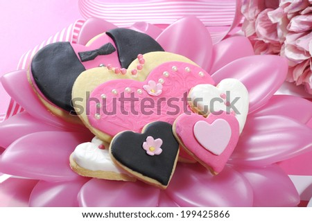Delicious wedding party bride and groom pink, white and black heart shape biscuit cookies bridal table favors on a pink and white decorated reception table - close up. . - stock photo
