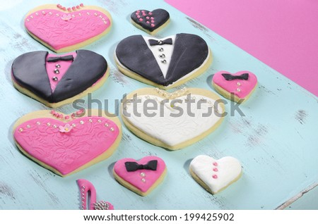 Delicious wedding party bride and groom with bridesmaid and groomsmen pink, white and black heart shape biscuit cookies bridal table favors with mini decorated hearts on a vintage blue tray. - stock photo