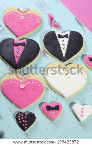 Delicious wedding party bride and groom with bridesmaid and grromsmen pink, white and black heart shape biscuit cookies bridal table favors with mini decorated hearts on a vintage blue tray. - stock photo