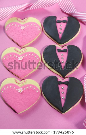 Delicious wedding party bridesmaids and groomsmen pink, white and black heart shape biscuit cookies bridal table favors on pink background. - stock photo