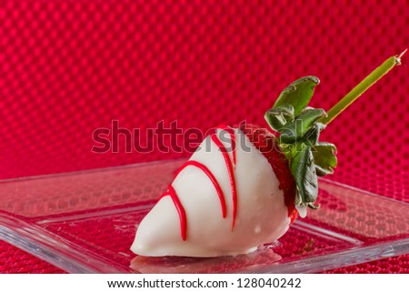 delicious white chocolate covered strawberry on a red background - stock photo