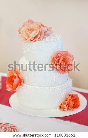 Delicious white wedding cake decorated with peonies - stock photo