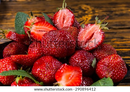 Delicious whole and halved juicy ripe red strawberries served in a bowl for a tasty summer dessert, overhead closeup view - stock photo