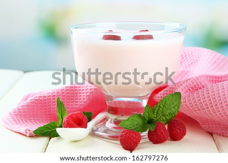 Delicious yogurt with berries on table on bright background