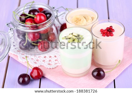 Delicious yogurt with fruits tastes in glasses and fresh fruits on color wooden background
