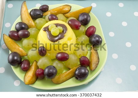 deliciously decorated fruit salad with vanilla pudding on a green plate with dotted backrgound - stock photo
