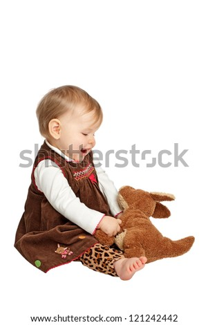 Delighted baby girl sits sideways holding stuffed toy kangaroo. She wears a brown velvet embroidered dress with leopard print pants. Isolated/cut out on white background, vertical, copy space,