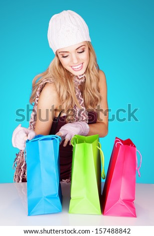 Delighted beautiful blond woman peeking into her brightly coloured shopping bags smiling happily at her new purchases
