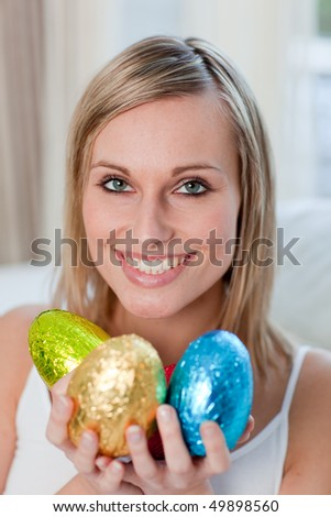 Delighted blond woman showing colorful Easter eggs - stock photo