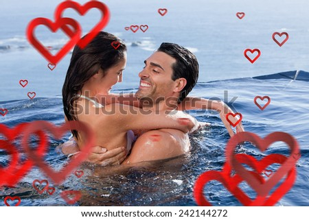 Delighted couple cuddling each other against love heart pattern - stock photo