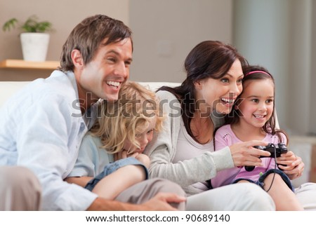 Delighted family playing video games together in a living room - stock photo