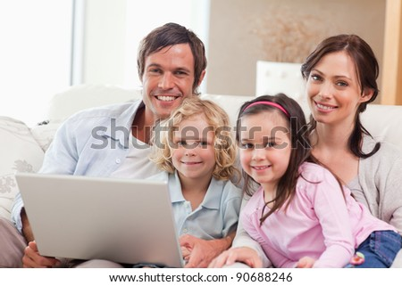 Delighted family using a laptop in a living room - stock photo