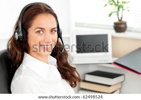 Delighted hispanic businesswoman with headset sitting at her desk in a call center - stock photo