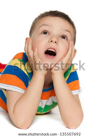 Delighted little boy is lying on the floor on the white background and looking up - stock photo