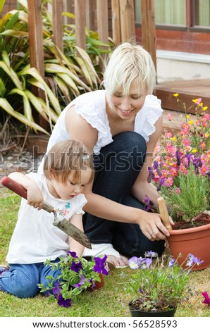 Delighted mother with her daughter outside with flowers - stock photo