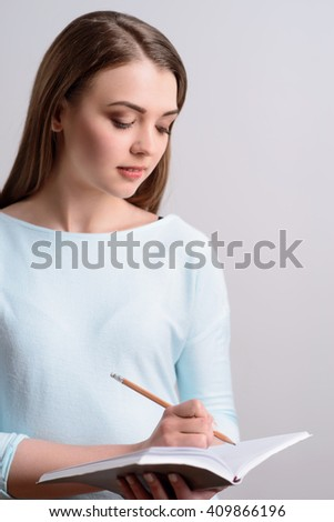 Delighted nice girl making notes
