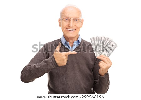 Delighted senior gentleman holding a stack of money and pointing towards them with his finger isolated on white background