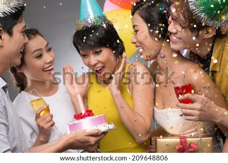 Delighted Vietnamese girl receiving a birthday cake from her friends - stock photo