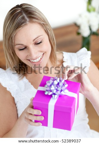 Delighted woman opening a gift sitting on the floor at home - stock photo