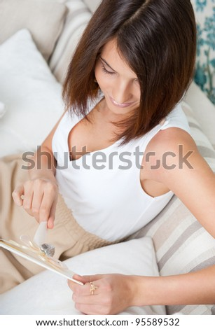 Delighted woman reading a valentine greeting card with heart and ribbon lying on the sofa at home. Top View - stock photo