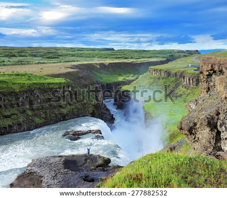 Delighted woman tourist on the shore of the huge waterfall Gyullfoss. Summer in Iceland - stock photo