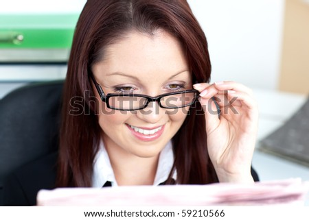 Delighted young businesswoman reading a newspaper in her office - stock photo