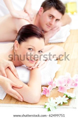 Delighted young couple receiving a back massage in a spa center - stock photo