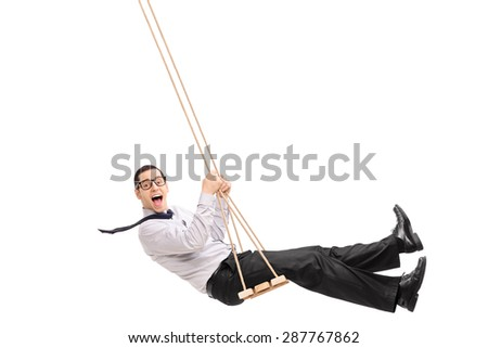 Delighted young man swinging on a swing and looking at the camera isolated on white background - stock photo