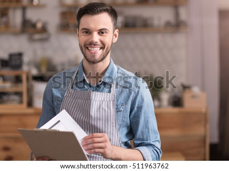 Delighted young smiling man holding a folder.