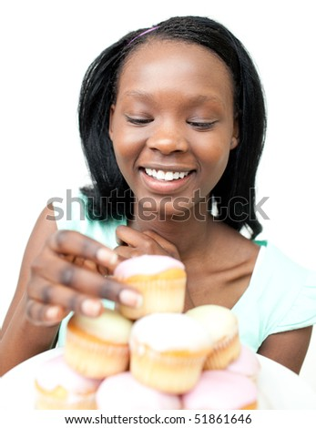 Delighted young woman looking at cakes against a white background - stock photo