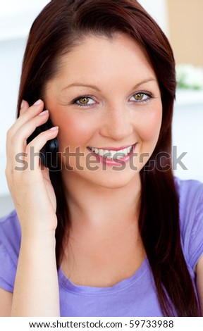Delighted young woman using her cellphone on a sofa at home