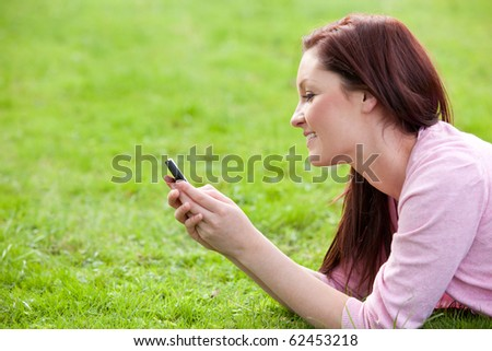 Delighted young woman writing a message on her phone sitting on the grass - stock photo