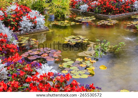 Delightful landscaped and floral park Butchart Gardens on Vancouver Island. Small pond, overgrown with flowers - stock photo