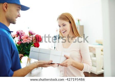 Delivery boy giving gift box and flowers to a surprised woman - stock photo